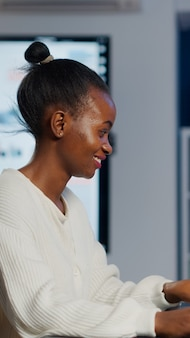 Zwarte freelancer-spelontwikkelaar die op toetsenbord typt en een nieuw niveau van videogame ontwikkelt. afrikaanse pro-speler test game over level-interface om middernacht vanuit kantoor met laptop. Premium Foto
