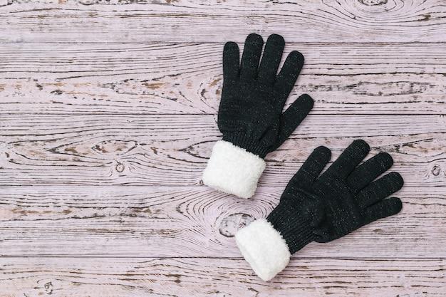 Zwarte gebreide dameshandschoenen met witte vacht op een houten ondergrond. mode winteraccessoires voor dames. plat leggen.
