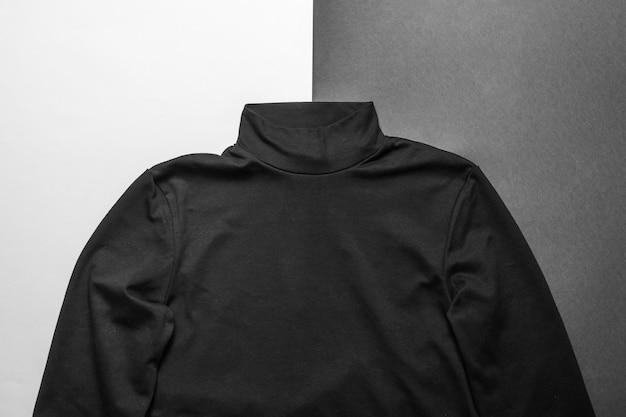 Zwarte gebreide trui voor heren op zwart-wit oppervlak. klassieke stijlvolle herenkleding.