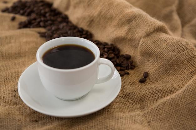 Zwarte gediende koffie en koffiebonen op zak