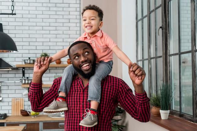 Zwarte gelukkige vader die zoon op schouders vervoert