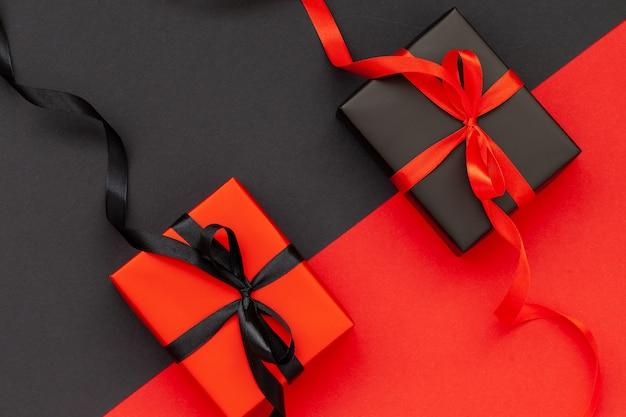 Zwarte geschenkdoos en rode huidige doos met op zwarte en rode achtergrond