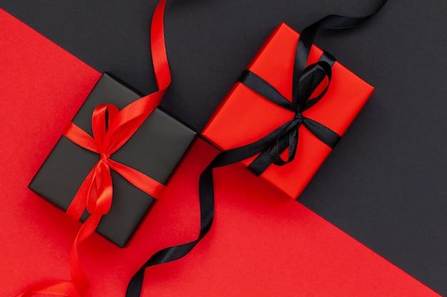 Zwarte geschenkdoos en rode huidige doos op zwarte en rode achtergrond