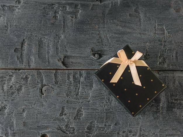 Zwarte geschenkdoos met gouden lint op zwarte tafel