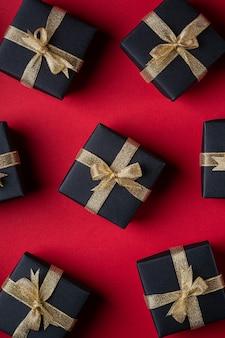 Zwarte geschenkdoos met gouden linten op rood papier
