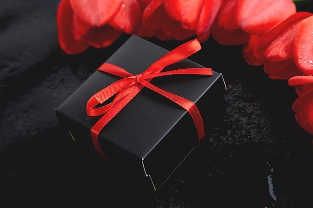 Zwarte geschenkdoos met rood lint in de buurt van rode tulp. plat liggen. moeder of vrouwendag. wenskaart. kopieer ruimte. voorjaar.