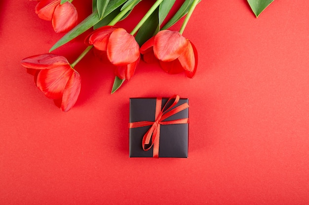 Zwarte geschenkdoos met rood lint in de buurt van rode tulp