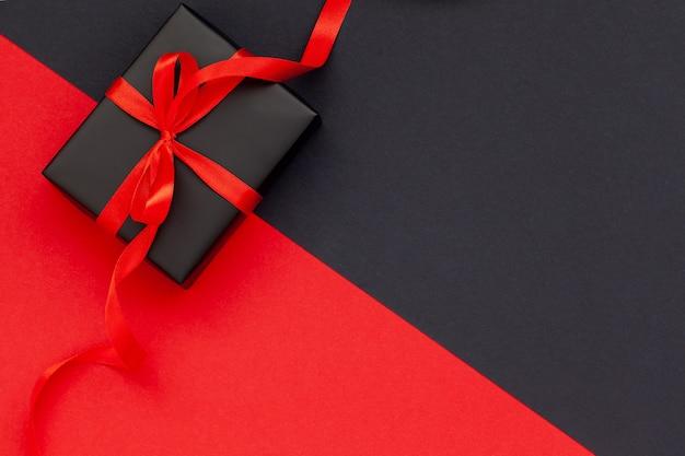 Zwarte geschenkdoos met rood lint op zwarte en rode achtergrond met kopie ruimte voor tekst