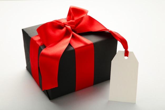 Zwarte geschenkdoos met verkoop tag op grijs