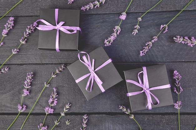 Zwarte geschenkdoos met violet ribbonnd boeket van lavendel bloem op zwart.