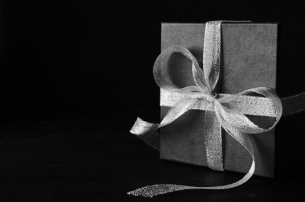 Zwarte geschenkdoos met zilveren strik op zwarte achtergrond.