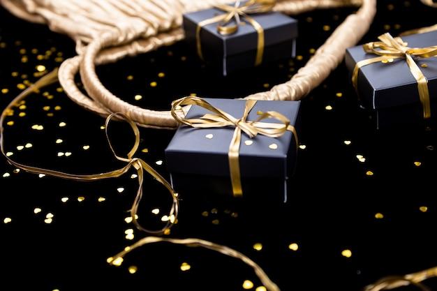Zwarte geschenkdozen met gouden lint springen uit de gouden zak op glanzende achtergrond