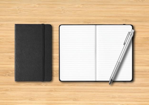 Zwarte gesloten en open gelinieerde notitieboekjes met een pen. mockup geïsoleerd op houten achtergrond