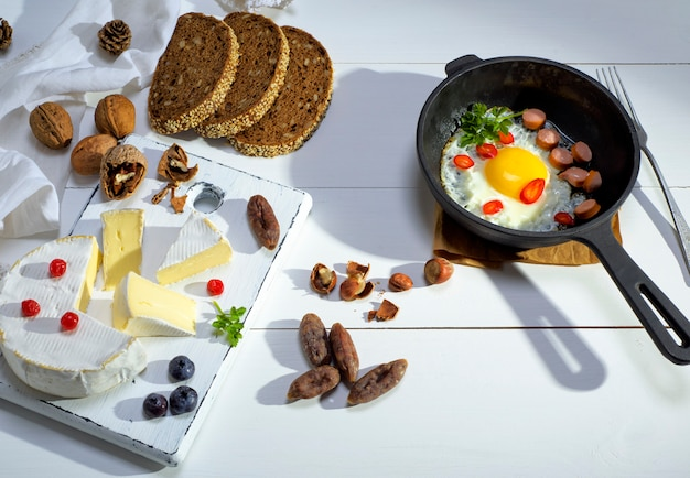 Zwarte gietijzeren koekenpan met gebakken ei en worst