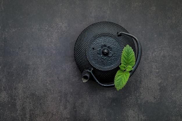 Zwarte gietijzeren theepot met kruidenthee opgesteld op donkere steen.