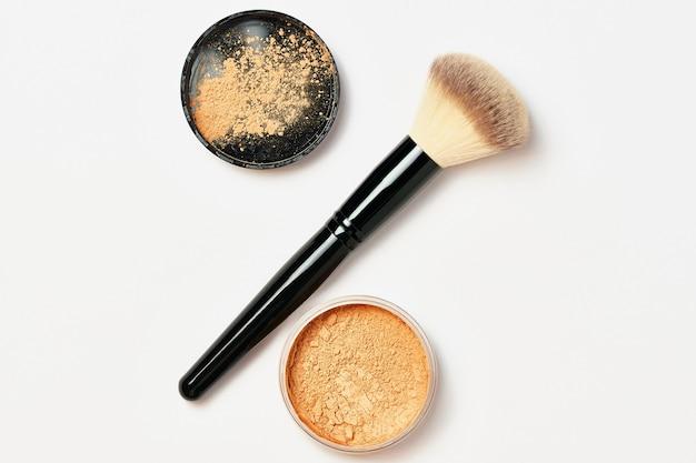 Zwarte glanzende make-upborstel met poederbasis die op wit wordt geïsoleerd. cosmetisch los poeder voor gezichtsmake-up in een open pot met een gezichtsborstel op een witte achtergrond. schoonheid en cosmetica concept.