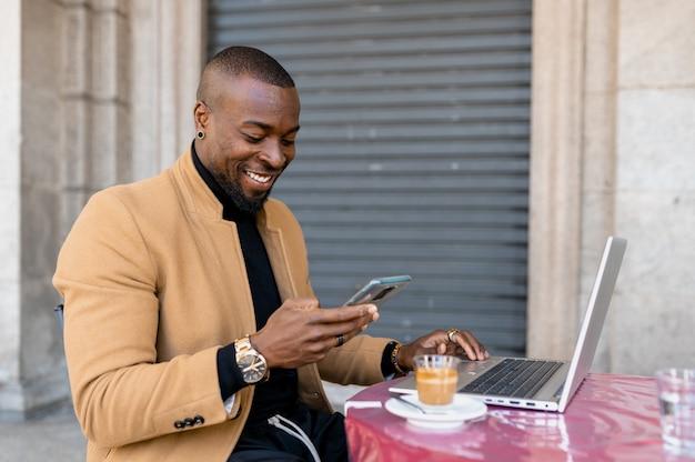 Zwarte glimlachende man met mobiele telefoon terwijl hij in een café zit met een laptop.