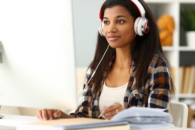 Zwarte glimlachende vrouwenzitting op werkplaats die hoofdtelefoons draagt