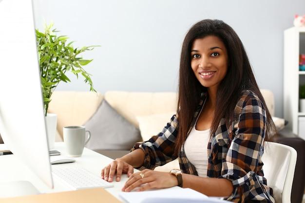 Zwarte glimlachende vrouwenzitting op werkplaats die met desktoppc werkt