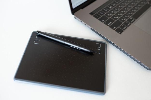 Zwarte grafische tablet met stylus en laptop. hulpmiddelen voor het retoucheren.