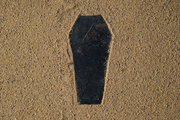 Zwarte grafvorm gemaakt op het zand