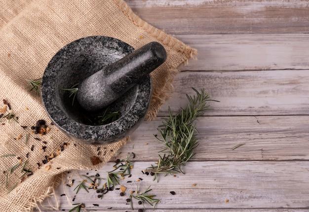 Zwarte granietmortel op beige keukendoek en houten ondergrond