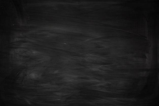 Zwarte grunge vuile textuur met copyspace. abstract krijt dat op bord of bordachtergrond wordt uitgewreven. behang met lege sjabloon en krijtsporen of massageconcept voor al uw ontwerp.