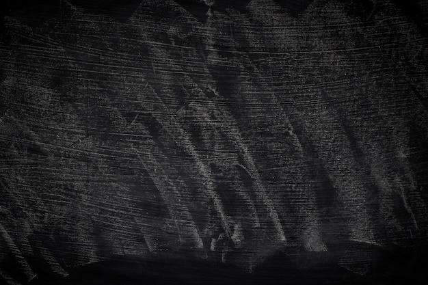 Zwarte grungetextuur met copyspace. abstract krijt dat op bord wordt uitgewreven.