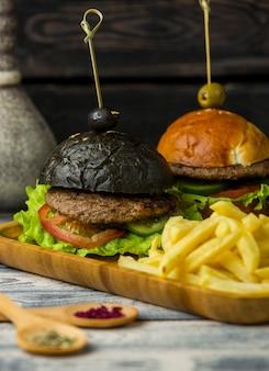 Zwarte hamburger en witte hamburger met frietjes in houten schotel
