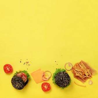 Zwarte hamburger, frietenaardappels, tomaten, kaas, ui, komkommer en sla op gele achtergrond. haal maaltijd weg. ongezond dieetconcept