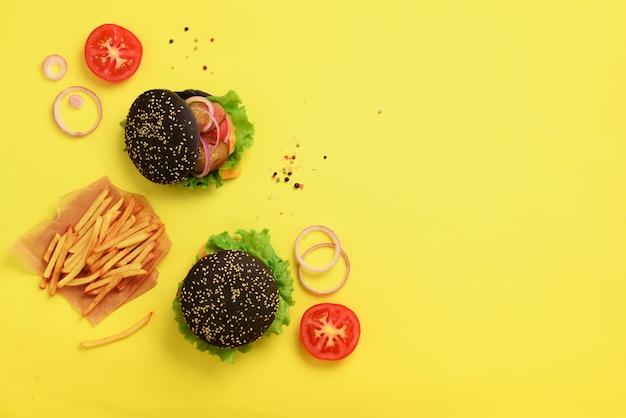 Zwarte hamburger, frietjes aardappelen, tomaten, kaas, ui, komkommer en sla op gele achtergrond.