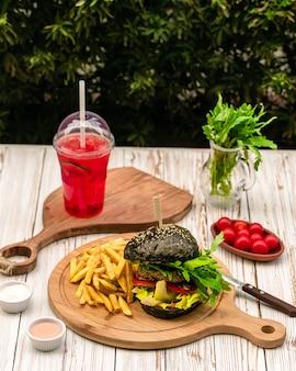 Zwarte hamburger geserveerd met friet