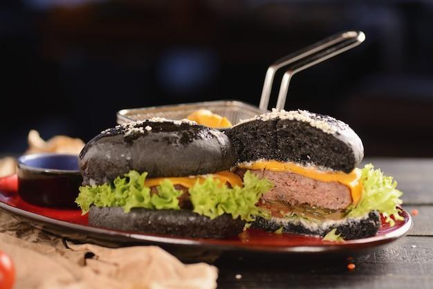 Zwarte hamburger met friet en saus. in een rode plaat op een houten tafel
