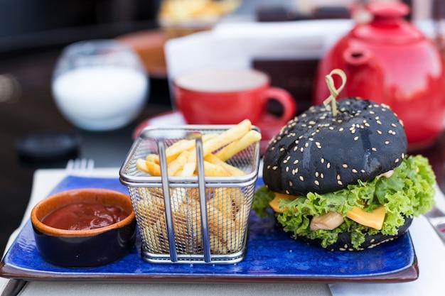 Zwarte hamburger met gebakken aardappelen en ketchup op een blauwe plaat