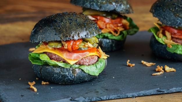 Zwarte hamburger met rundvlees en tomaten saus