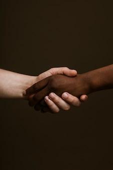 Zwarte hand die de witte hand vasthoudt