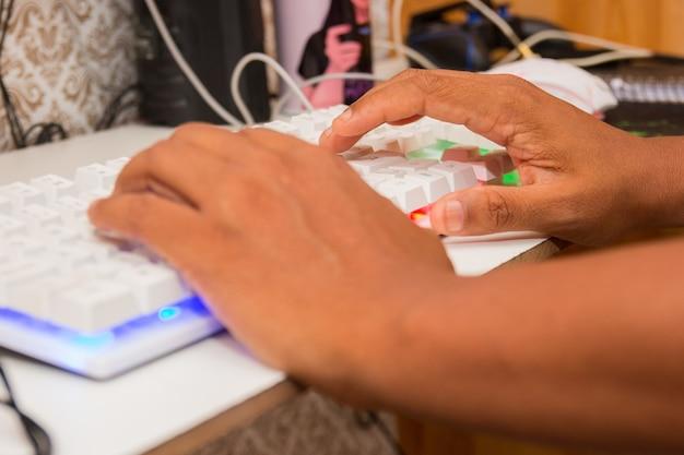 Zwarte handen die op een gamertoetsenbord typen in brazilië.