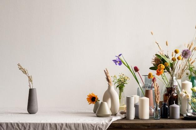 Zwarte handgemaakte kruik van keramiek of klei met gedroogde wilde bloemen op tafel met grote groep kaarsen en creatieve vazen met bloemen