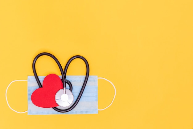 Zwarte hartvormige stethoscoop op medisch beschermend masker en rood document hart