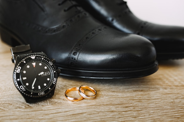 Zwarte herenschoenen op de grond met gouden trouwringen en mechanische polshorloges