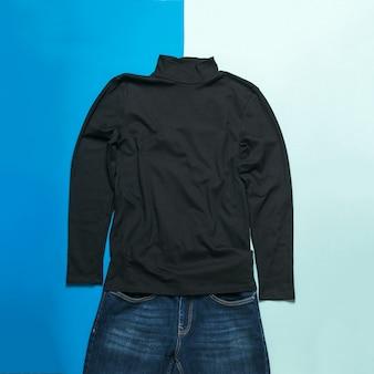 Zwarte herentrui en jeans op een tweekleurige ondergrond. stijlvolle herenkleding.