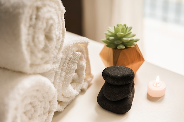 Zwarte hete steen; brandende kaars; cactus plant en opgerolde witte handdoek