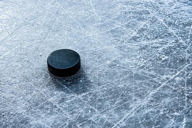 Zwarte hockeypuck ligt op ijs in het stadion