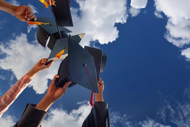 Zwarte hoed van de afgestudeerden zwevend in de lucht.