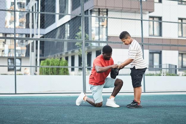 Zwarte honkbalspeler die op één knie zit terwijl hij een honkbalhandschoen aan zijn zoon geeft voor de wedstrijd in de buitenspeeltuin