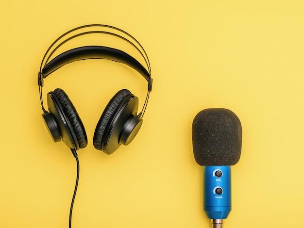 Zwarte hoofdtelefoon en blauwe microfoon op gele achtergrond. apparatuur voor het opnemen, communiceren en luisteren naar muziek.