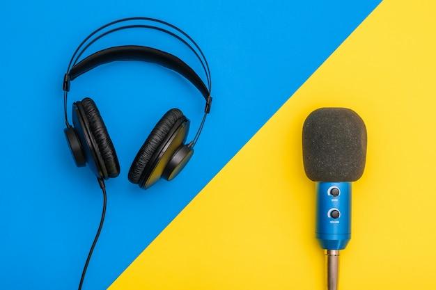 Zwarte hoofdtelefoon en blauwe microfoon op lichtgeel en blauw.