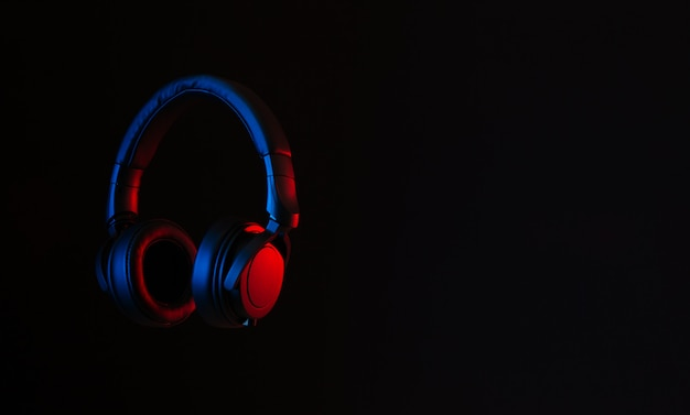 Zwarte hoofdtelefoon op abstracte achtergrond verlicht met rode en blauwe neonlichten