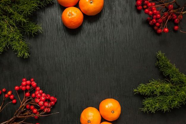 Zwarte houten achtergrond met mos en as en mandarijnen aan de zijkanten. grunge textuur