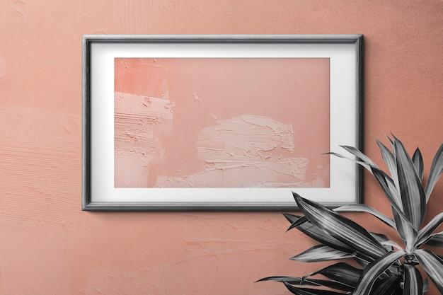 Zwarte houten fotolijst met perzikkleur schilderij op de muur